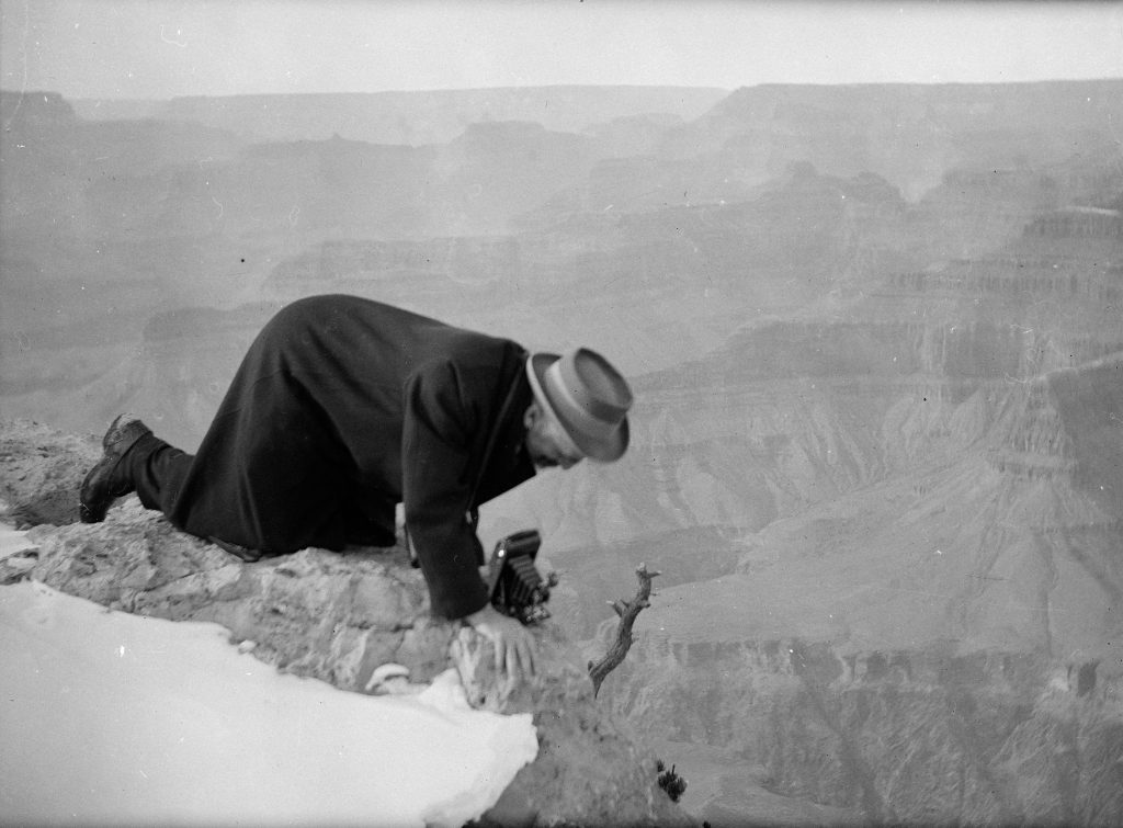 A black and white photograph of Dow on hands and knees at the rocky edge of the Grand Canyon, bending over a camera on the ground in front of him.