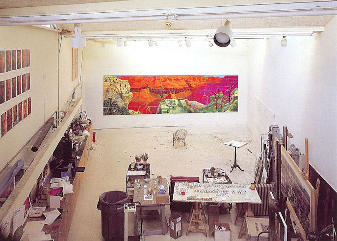 A photograph of Hockney's studio with The Grand Canyon painting covering much of the far wall.