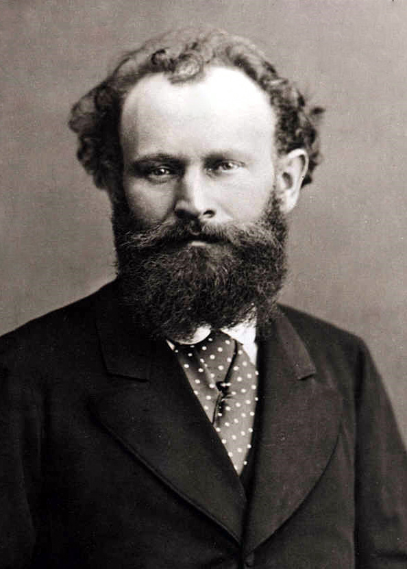 A black and white headshot-style photograph of Manet, wearing a suit and a polka dot cravat in front of a blank background.