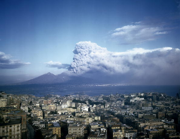 A photograph of the erupting Mount Vesuvius with clouds and smoke in the background and Naples in the foreground.