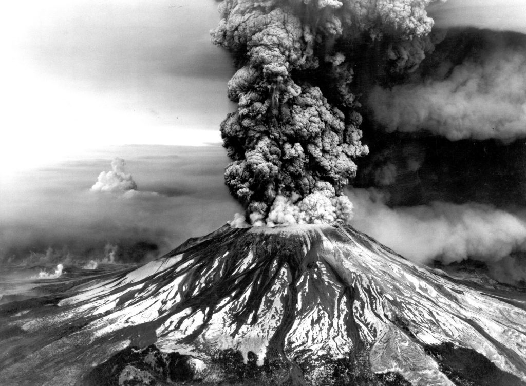 A photograph of Mt Saint Helens erupting in a column of dark smoke and ash.