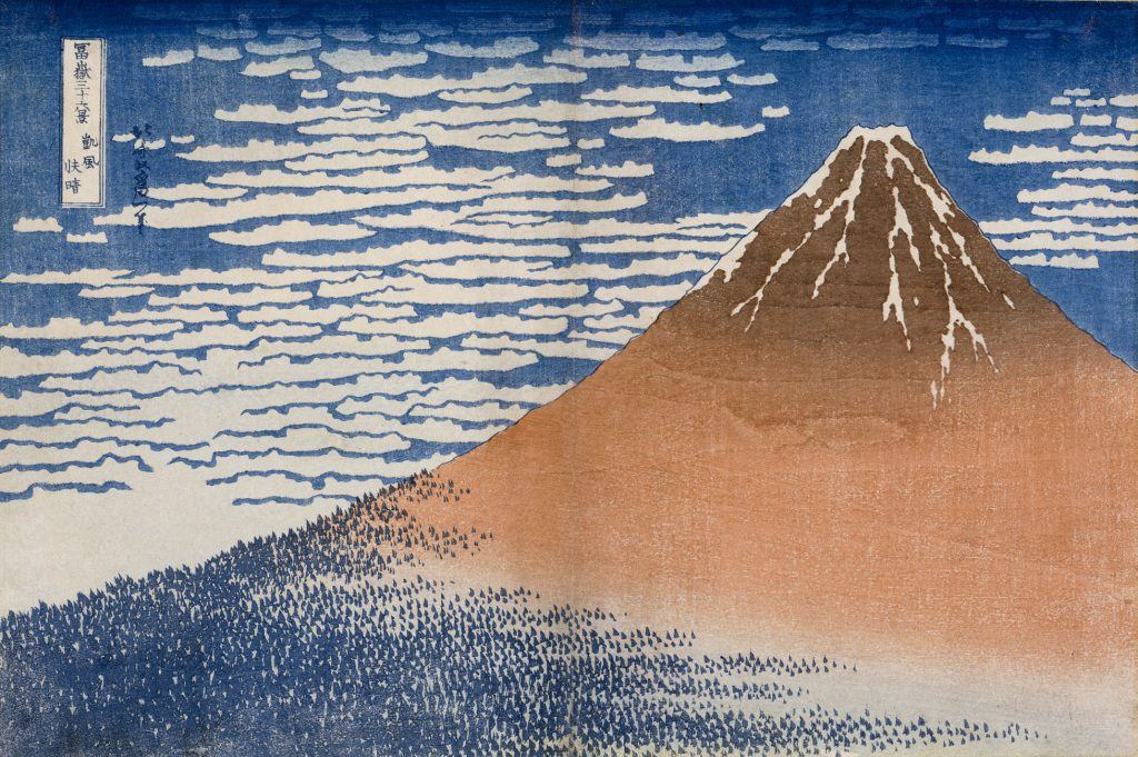 A woodblock print of a single tall brown mountain, its peak streaked with snow and base dotted with blue, over a background of deep blue sky and lined with clouds.